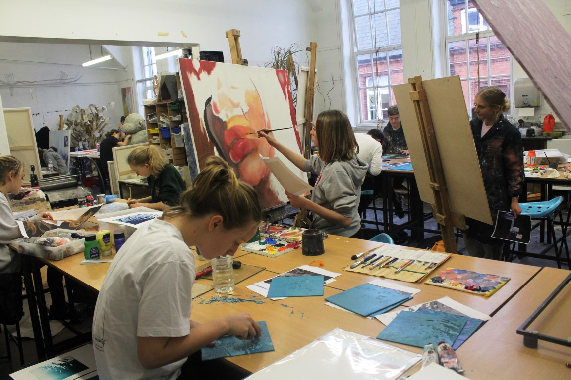 A group of pupils working on painting and drawing in an art room