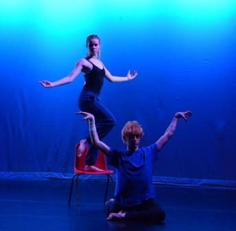 A girl holds a dance position on a chair, behind a boy holding a mirroring position on the floor in front.