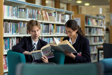 a girl and a boy read in the library
