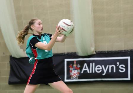 An Alleyn's middle school girl catches the ball mid-flight