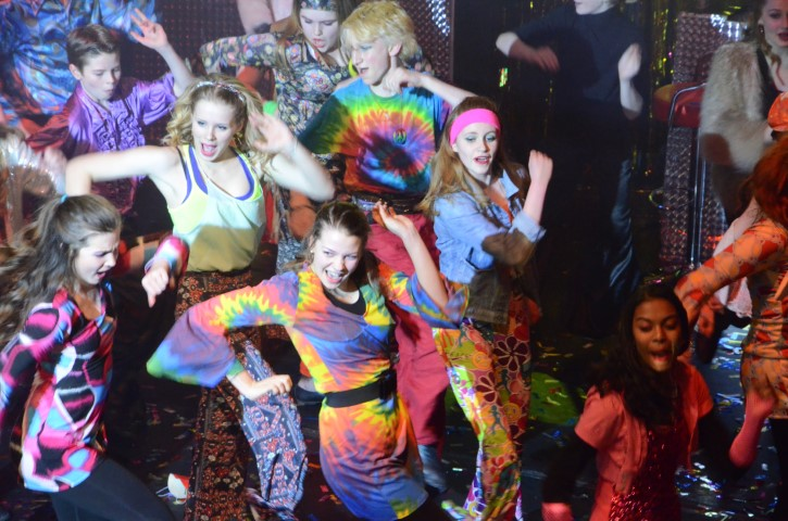 Boys and girls dance as part of the Disco Inferno production