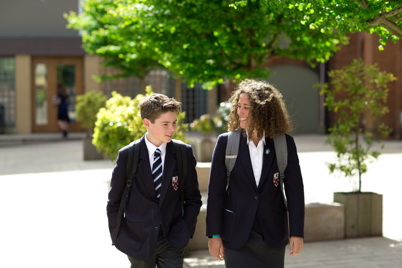 A boy and girl stroll across the School quad together